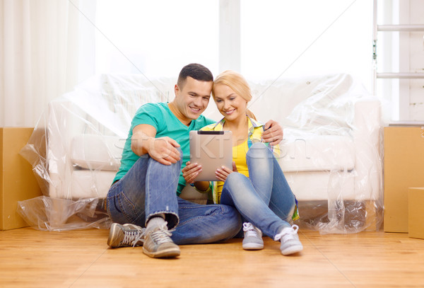smiling couple with tablet pc in new home Stock photo © dolgachov