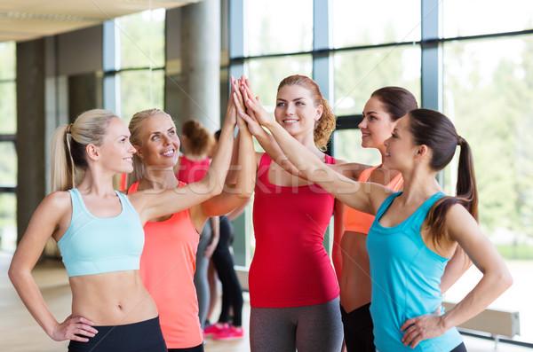 Grupo mulheres high five gesto ginásio Foto stock © dolgachov
