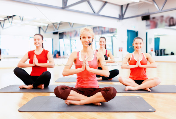 group of smiling feamle meditating in the gym Stock photo © dolgachov