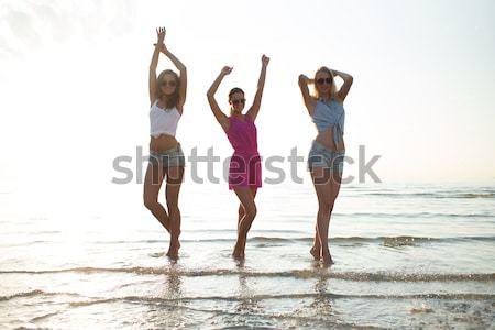 グループ 笑みを浮かべて 女性 を実行して ビーチ 夏休み ストックフォト © dolgachov
