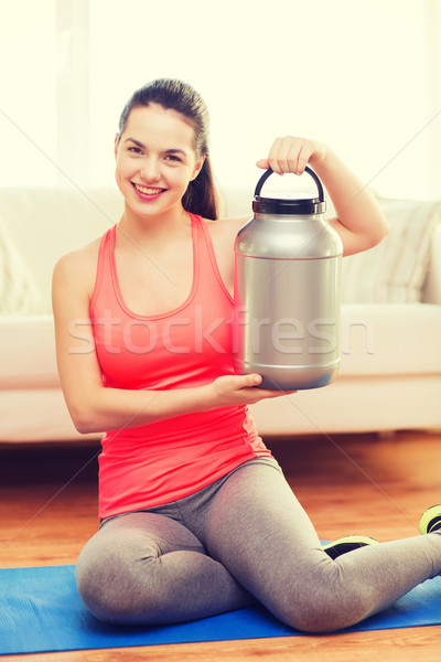smiling teenage girl with jar of protein at home Stock photo © dolgachov