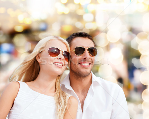 happy couple in shades over lights background Stock photo © dolgachov