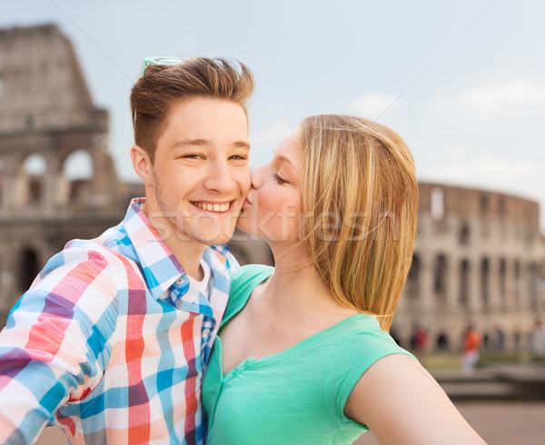 couple kissing and taking selfie over coliseum Stock photo © dolgachov
