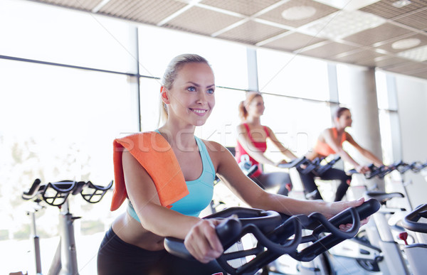 group of women riding on exercise bike in gym Stock photo © dolgachov