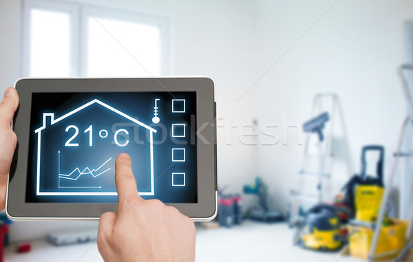 close up of tablet pc in hands setting temperature Stock photo © dolgachov