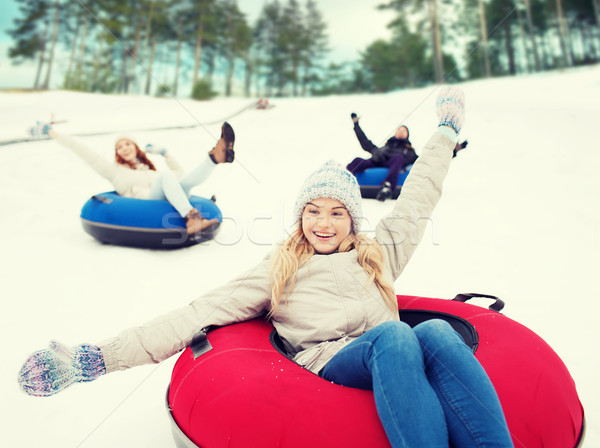 group of happy friends sliding down on snow tubes Stock photo © dolgachov
