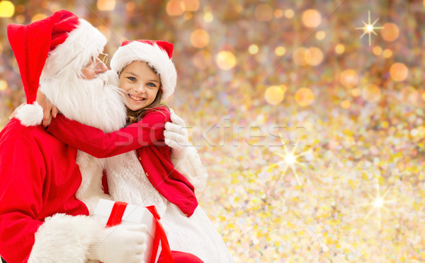 smiling girl cuddling with santa claus over lights Stock photo © dolgachov