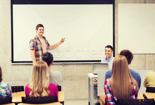 group of students and smiling teacher in classroom Stock photo © dolgachov