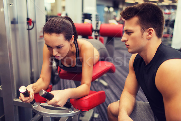 young woman with trainer exercising on gym machine Stock photo © dolgachov