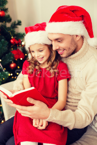 smiling father and daughter reading book Stock photo © dolgachov