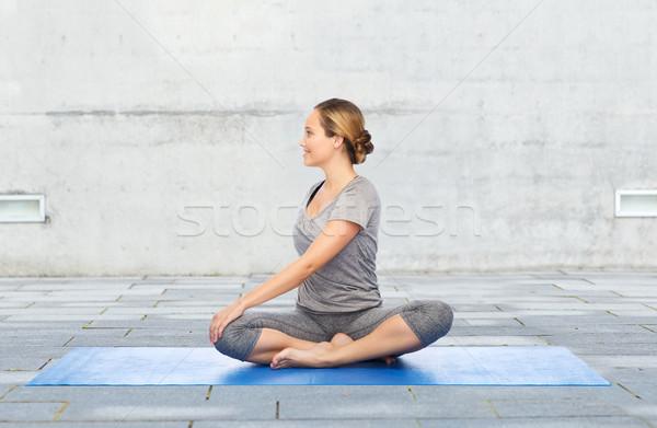 woman making yoga in twist pose on mat Stock photo © dolgachov