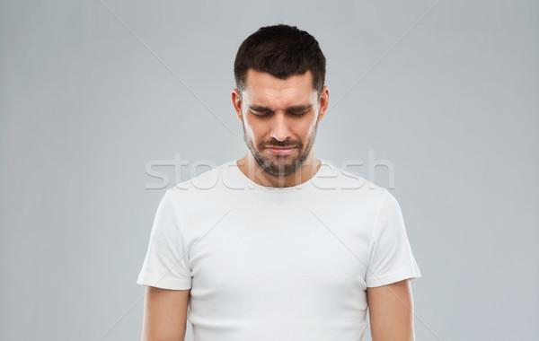 unhappy young man over gray background Stock photo © dolgachov