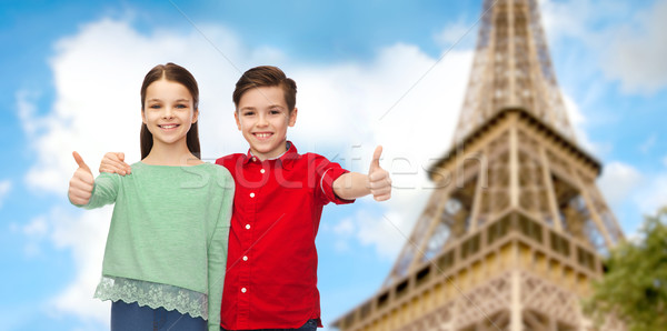 boy and girl showing thumbs up over eiffel tower Stock photo © dolgachov
