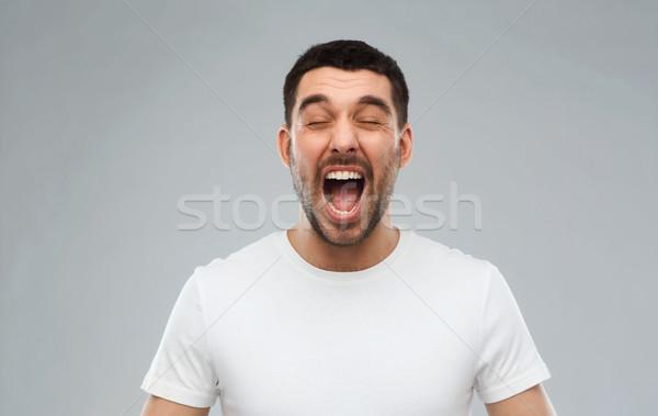 crazy shouting man in t-shirt over gray background Stock photo © dolgachov