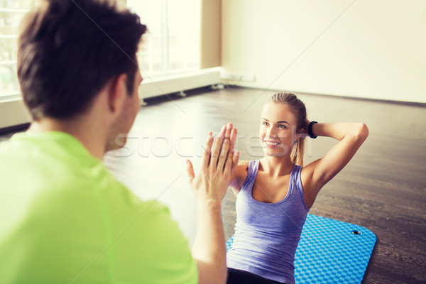 Stock photo: woman with personal trainer doing sit ups in gym