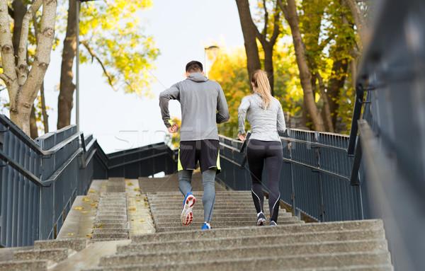 couple running upstairs in city park Stock photo © dolgachov