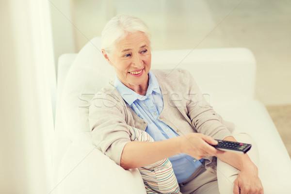 happy senior woman watching tv at home Stock photo © dolgachov
