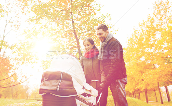 smiling couple with baby pram in autumn park Stock photo © dolgachov