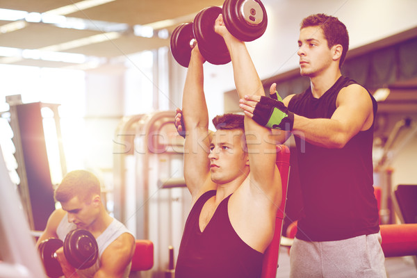 group of men with dumbbells in gym Stock photo © dolgachov