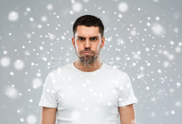 man with funny angry face over snow background Stock photo © dolgachov