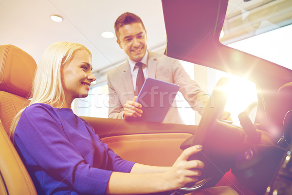 happy woman with car dealer in auto show or salon Stock photo © dolgachov