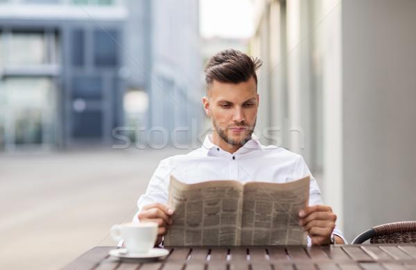 smiling man reading newspaper at city street cafe Stock photo © dolgachov