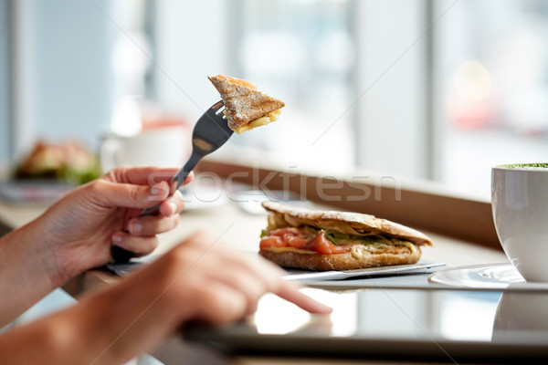 woman with tablet pc and panini sandwich at cafe Stock photo © dolgachov