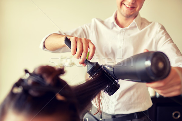 close up of stylist making hairdo at salon Stock photo © dolgachov