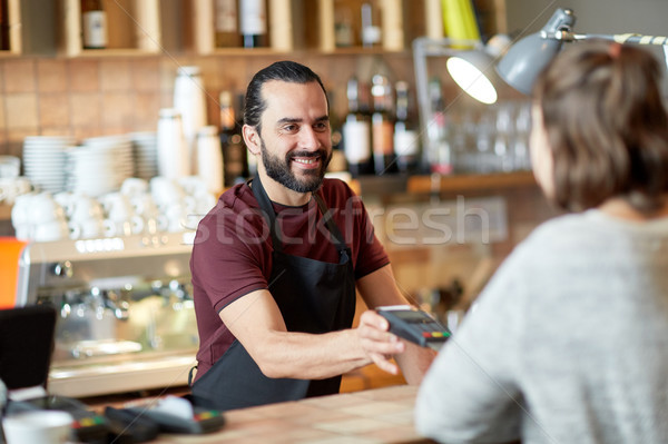 man or waiter with card reader and customer at bar Stock photo © dolgachov