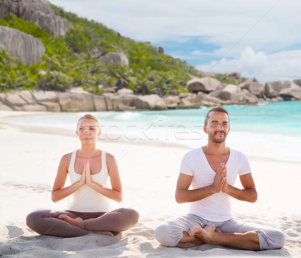 smiling couple making yoga exercises on beach Stock photo © dolgachov