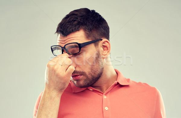 tired man with eyeglasses touching nose bridge Stock photo © dolgachov