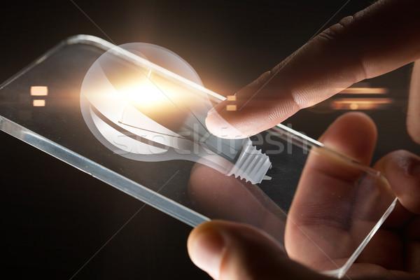 Mani smartphone lampadina proiezione uomini d'affari tecnologia Foto d'archivio © dolgachov