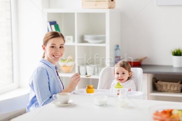 happy mother feeding baby with puree at home Stock photo © dolgachov