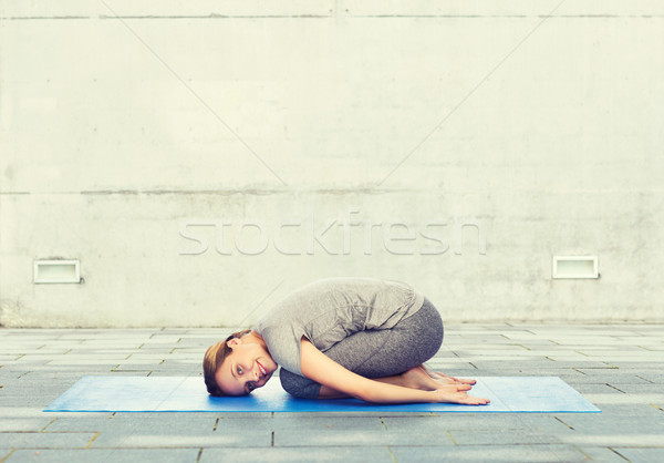 happy woman making yoga in child pose on mat Stock photo © dolgachov