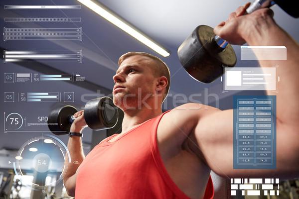 Fiatalember súlyzók izmok tornaterem sport testépítés Stock fotó © dolgachov