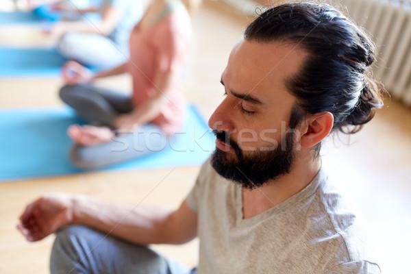 man with group of people meditating at yoga studio Stock photo © dolgachov