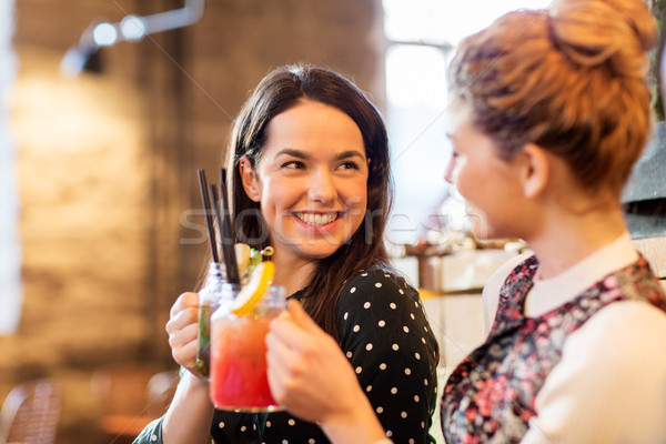 happy friends clinking drinks at restaurant Stock photo © dolgachov