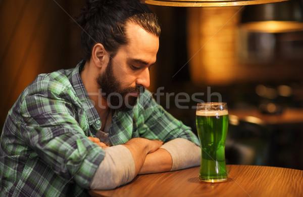 lonely man drinking green beer at bar or pub Stock photo © dolgachov
