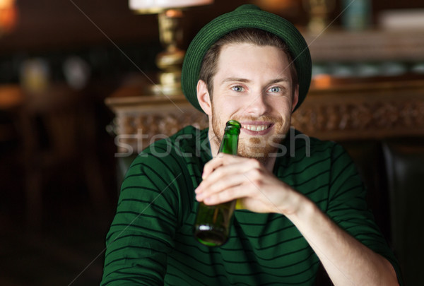 man drinking beer from green bottle at bar or pub Stock photo © dolgachov