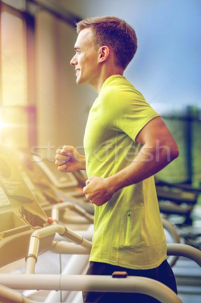 Mosolyog férfi testmozgás futópad tornaterem sport Stock fotó © dolgachov