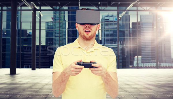 man in virtual reality headset with gamepad Stock photo © dolgachov