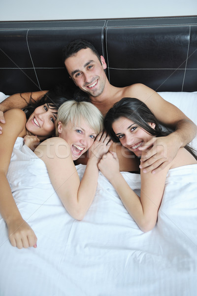 Young handsome man lying in bed with three girls Stock photo © dotshock