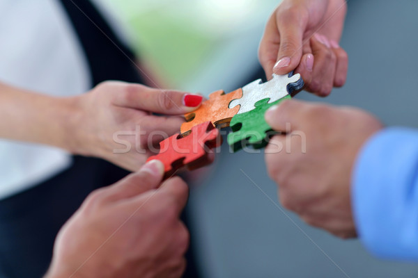 Stock photo: Group of business people assembling jigsaw puzzle