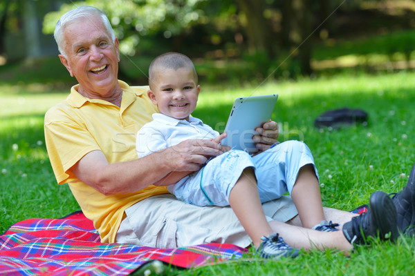 grandfather and child in park using tablet Stock photo © dotshock