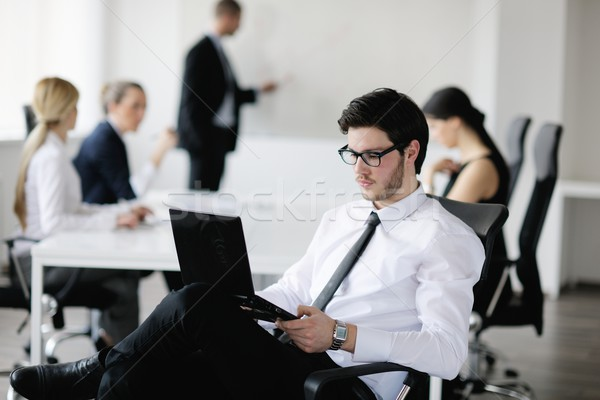 Stock photo: Portrait of a handsome young business man with colleagues in background