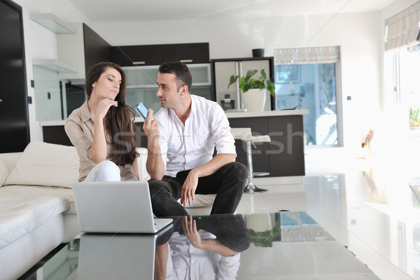 joyful couple relax and work on laptop computer at modern home Stock photo © dotshock