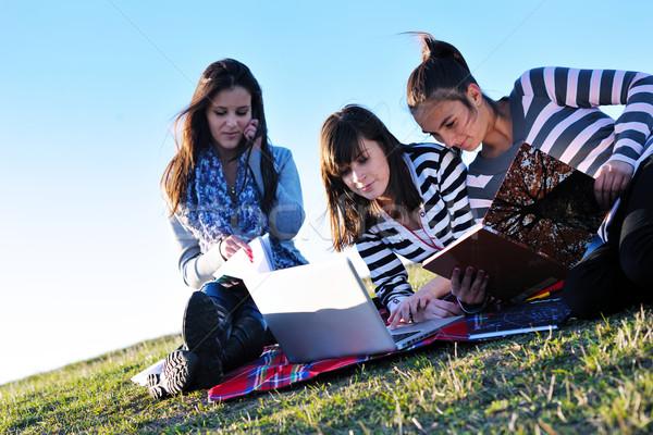 group of teens working on laptop outdoor Stock photo © dotshock
