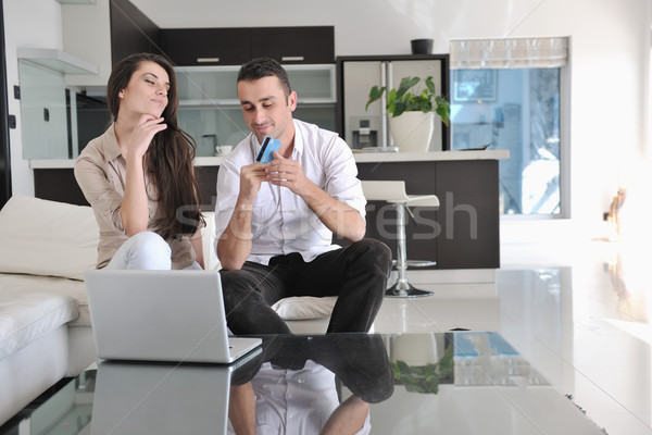 Stock photo: joyful couple relax and work on laptop computer at modern home
