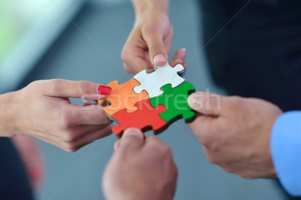Group of business people assembling jigsaw puzzle Stock photo © dotshock
