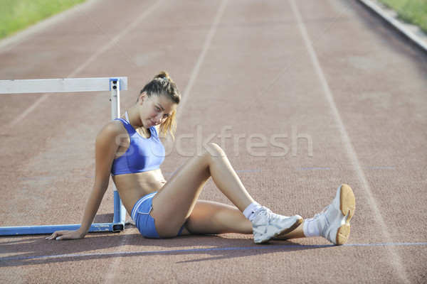 happy young woman on athletic race track Stock photo © dotshock